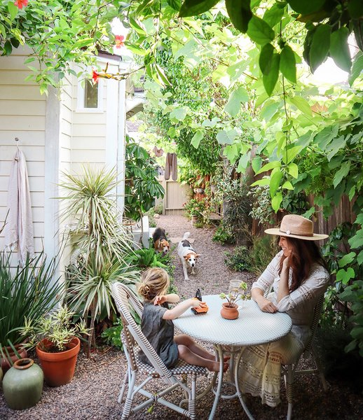 Whitney Leigh Morris and her son West sit at a bistro table in the side garden of their tiny cottage in Venice, California.