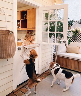 A Dutch door provides access from the kitchen to the porch, where West plays with the family's two rescue beagles, StanLee and Sophee.