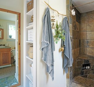 Whitney placed storage baskets and tins on the bathroom's open shelves to avoid visual clutter. A found branch functions as a towel rack beside the shower.