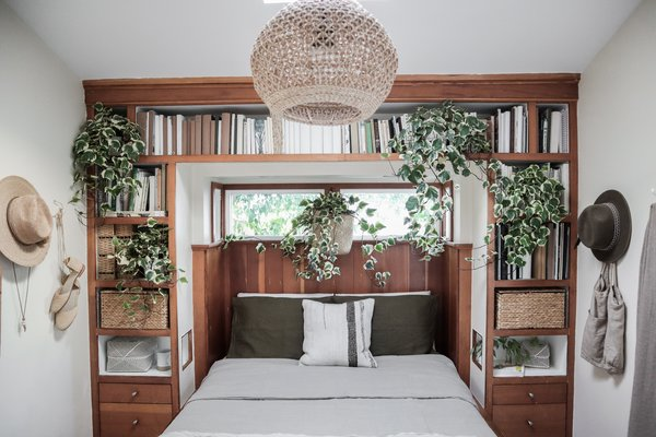 "Whitney created a fresh aesthetic for the bedroom by suspending a woven pendant above the bed and adorning the built-in shelves with basket organizers and plenty of cascading plants. ""[The bedroom is] small but highly functional thanks to the built-in bookshelf headboard and the concealed storage beneath the bed,"" says Whitney."