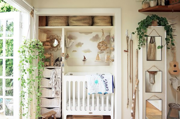 "When their son was an infant, Whitney and her husband Adam converted the bedroom closet into a stylish nursery. ""We removed select built-in features, such as a shoe rack, and painted the wood white in order to make the space more flexible and cheerful,"" she says. ""Our son now sleeps on our built-in couch thanks to a simple bumper pillow and a set of dedicated sheets, and the closet is once again where we keep all of our clothing as a family."""