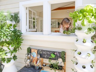 A garden work bench and recycled plastic towers planted with vegetables, herbs, and fruit are situated on the porch.