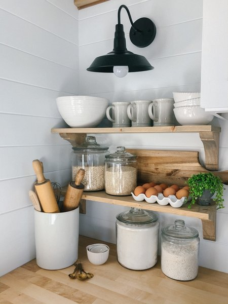 An industrial-style metal sconce, ceramic tableware, and wood countertops lend a farmhouse aesthetic to the kitchen.