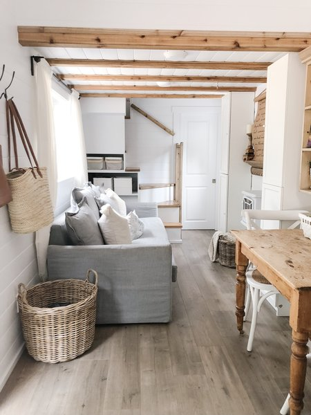 Wood beams contrast with the white shiplap walls in the living area, where the adults sleep on a pull-out sofa.