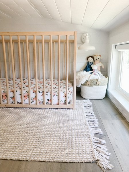Emma arranged Ivy's room with a custom wood crib, a white-painted metal sconce, and a rug from HomeSense.