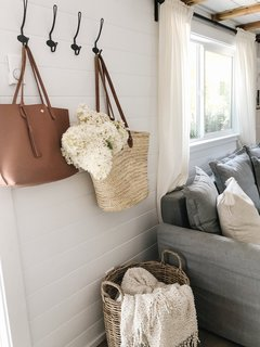 Metal hooks hang on white shiplap walls in the sun-drenched entry. Woven accents supply texture and warmth.