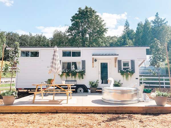 The cedar-clad tiny house Emma McAllan-Braun and Joel Braun created with Mint Tiny Homes features a pine deck with a stock tank swimming pool.
