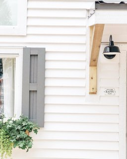 Window shutters, planted window boxes, white-painted cedar siding, and an industrial-style metal sconce enliven the exterior the farmhouse-style tiny home.