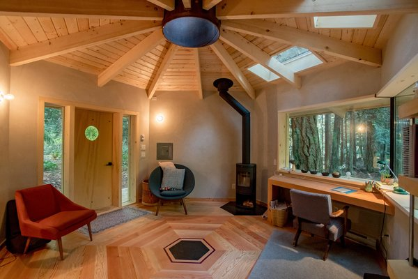 Douglas Fir floor boards are laid in a hexagonal pattern on the interior of the studio, where clay plaster walls lend warmth and texture. Skylights flood the space with plenty of sunlight.