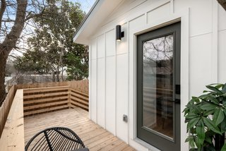 The Williamsons clad the tiny home with bright white board-and-batten and selected a dark gray tone for the entry door and the fascia.