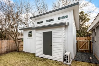 A bump-out on the rear facade of the tiny home holds outdoor equipment, referencing the shed that once stood in its place.