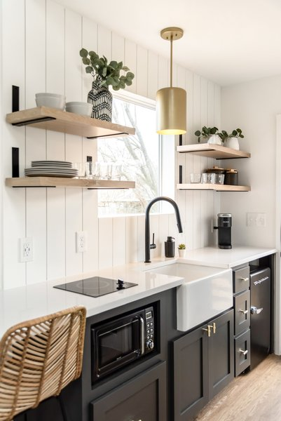 The kitchen is outfitted with open shelving, gray-painted wood cabinetry, white Silestone counters, and a white-painted shiplap backsplash.