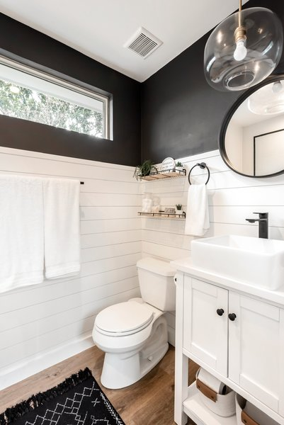Shiplap, a wood vanity, and wood-style vinyl flooring lend texture and warmth in the bath.