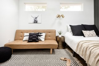 Lauren arranged the living area with a fold-out sofa from Urban Outfitters, a sconce from Living Spaces, and artwork and a woven rug from Target.