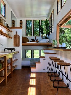 The living room is situated just above the main-level bedroom at one end of the combined kitchen and dining area, where spotted gum flooring contrasts with white-painted pine walls.