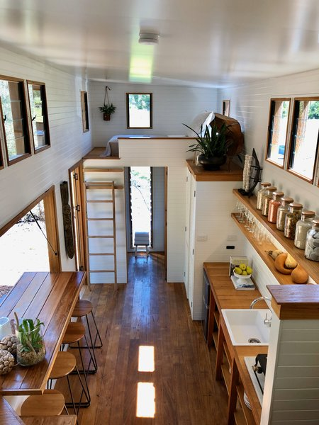 """The interior of the tiny home, furnished by Simone Bennett-Smith, is marked by rich texture and a neutral palette. """"Simone has always preferred an eclectic, coastal style with lots of references to travel,"""" Adam says. """"We like natural colors and the warmth of wood."""""""