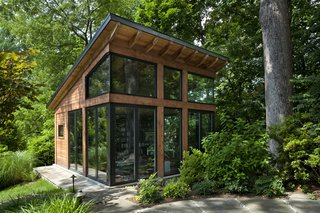 The studio is clad with cedar, glass, and a sloping, standing-seam metal roof.