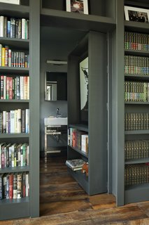 One section of the floor-to-ceiling bookshelves pivots open to reveal a concealed bathroom.