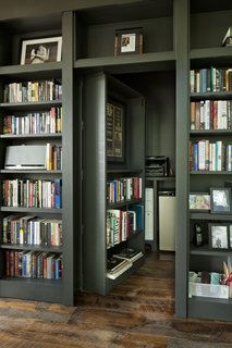A minibar and storage area are hidden behind another section of the floor-to-ceiling bookshelves.