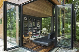 The NanaWall doors on the corners of the front facade fold open, joining the interior and the wooded landscape.