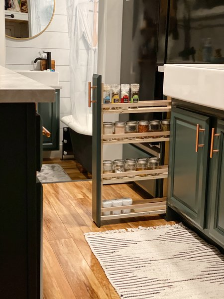 A narrow spice rack pulls out from the cabinetry and offers efficient storage in the kitchen.