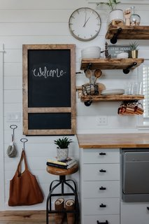 A wood-framed chalkboard folds down from a wall in the kitchen and provides more counter space and a dining area. The open wood shelving was crafted from a beloved table that did not fit in the tiny home.