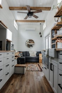 White-painted pine shiplap and wood ceiling beams lend texture on the interior, where pale gray cabinetry offsets wood-like vinyl flooring.