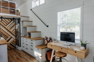 The Perezes created an office area, storage beneath the stairs, and a sliding door that sections the kitchen from the bathroom.