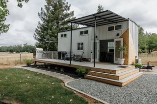 The tiny home is clad with standing-seam metal and cedar. An outdoor kitchen area on the deck provides added living space and ties the home to the natural landscape.