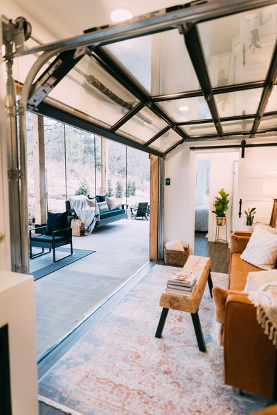 An aluminum-framed garage-style glass door that's motorized rolls up and links the interior of the home to its wooded surround.