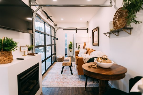 The open-plan interior is outfitted with a round wood table and upholstered chairs in the dining area and a leather-covered sofa and a wood bench-turned-coffee table in the living space.