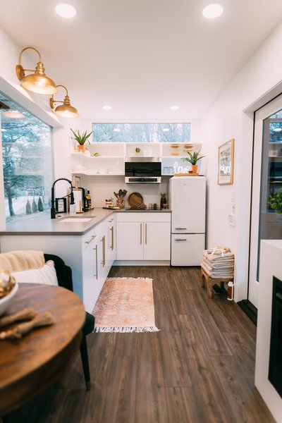 """We knew we wanted the kitchen to have a beautiful view of the outdoors so we designed a large picture window that allows you to admire the scenery,"" Dianna says. Low maintenance coffee-colored vinyl flooring offsets the room's bright white cabinetry."