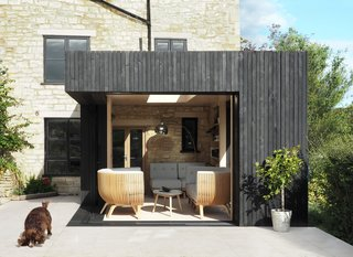 The garden library that architect George King designed to accompany a 17th-century limestone house and its surrounding gardens in England is clad with charred timber and large glass doors that slide open and connect the structure to the outdoors.