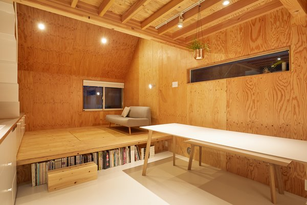 The living space steps up from the kitchen-and-dining area and features a plywood floor, ceiling and walls.