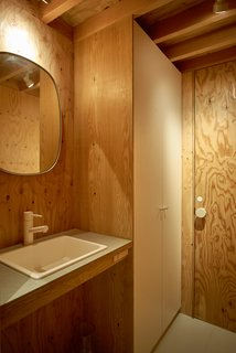The bathrooms are wrapped in raw plywood that lends organic texture, warmth and pattern to the interior.