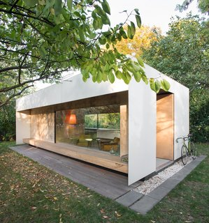 """The micro home in Warsaw that architect Adam Pszczolkowski designed for his family and friends features expansive windows framed by plywood and white-painted HPL panels. """"I chose white because of its modern and timeless character,"""" the architect says."""