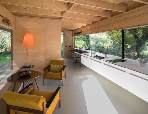 """A pair of 1970s velvet-upholstered armchairs flank a midcentury-style wood table in the living area. The kitchen features a line of cabinets suspended above the epoxy resin floor. """"The glazing on the east side is as long as the facade and spans eight meters,"""" the architect says. """"It's adjusted and harmonized with the kitchen worktop."""""""