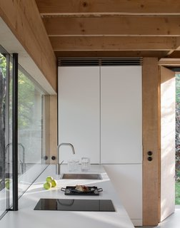 Like the home's exterior, the kitchen features a pale palette, which lends a fresh aesthetic.