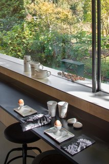 Arranged with a low-lying counter and stools, the glazed dining area evokes the sensation of dining outdoors.