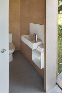 The bathroom is also outfitted with plywood walls and an epoxy resin floor.