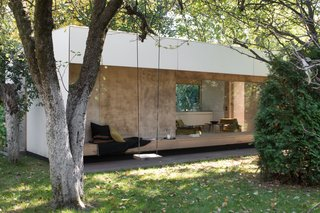 """""""Without opening an umbrella, we can relax using the exterior long wood bench that's shaded by the roof's overhang,"""" Adam says."""