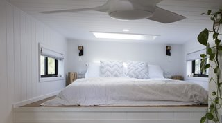The master sleeping loft features a skylight and windows on either side of the bed that create a cross breeze.