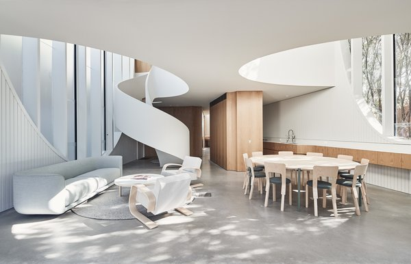 A ribbon-like spiral staircase leads from the open-plan living area to the second level, where the bedrooms are located.