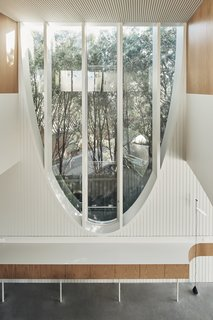 The wide upper portion of the arched window in the kitchen/dining space brings sunlight into the interior.