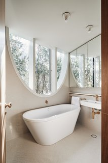 The trees around the home help to filter and soften the sunlight that pours into this bath on the second level.
