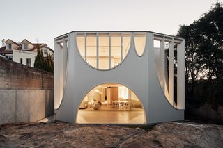 The rear facade features a covered outdoor area. An arched opening connects to the interior on the backyard.