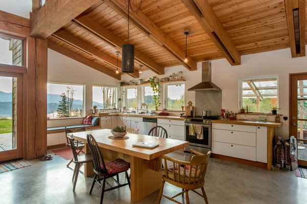 The open-plan kitchen-and-dining space features a Douglas fir ceiling and ceiling beams and polished concrete floors.