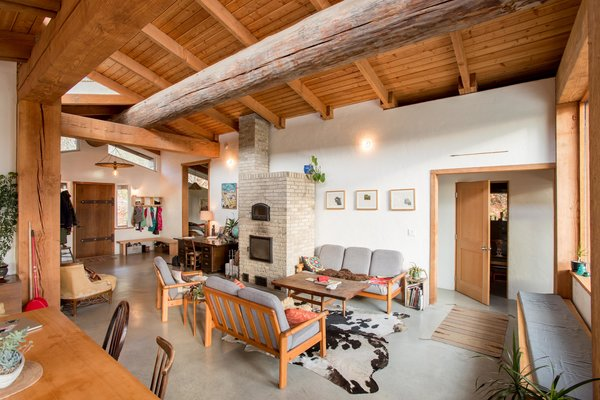 The large, round Douglas fir trunk contrasts with the rectangular ceiling beams and provides raw, organic texture in the open-plan living room.