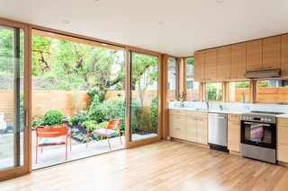 Glass walls and sliding doors connect the first level to the lush yard and garden.