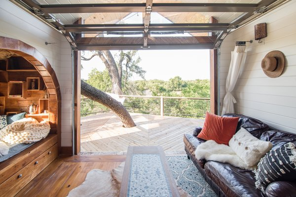 A massive industrial-style door rolls up and ties the living area and the book nook to the outdoors, where a large tree punctures the wood decking.